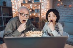 Grandfather and grandson are watching movie with popcorn at night at home. Grandfather and grandson are watching movie with popcorn at table at night at home Royalty Free Stock Photo