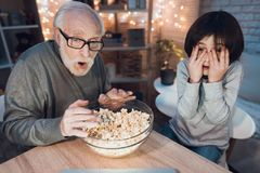 Grandfather and grandson are watching scary movie at night at home. Grandfather and grandson are watching scary movie at table at night at home Royalty Free Stock Photos