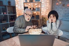 Grandfather and grandson are watching scary movie at night at home. Grandfather and grandson are watching scary movie at table at night at home Royalty Free Stock Images