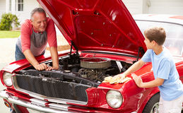 Grandfather And Grandson Working On Restored Classic Car Royalty Free Stock Images