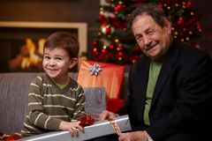 Grandfather and grandson wrapping gifts together Stock Photos