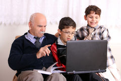 Grandfather, grandsons and notebook. Boy playing on the computer while grandfather teaching it Royalty Free Stock Photos