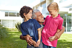 Grandfather having fun with grandchildren. Grandfather having fun with his two grandchildren in a garden in front of a house Royalty Free Stock Photography