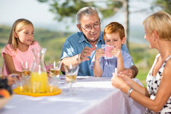 Grandfather having fun in playing cards game Royalty Free Stock Image