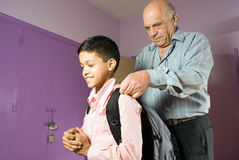 Grandfather helping grandson get ready to leave - Stock Images