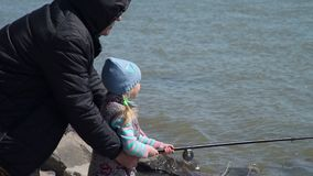 Grandfather helping his granddaughter to fish. Senior man helping young girl to cast a fishing pole. Grandfather and granddaughter are fishing in spring. The stock video footage