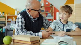 Grandfather helping junior child with homework talking sitting at desk together