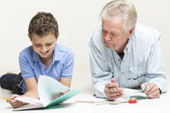 Grandfather helps his grandson with homework royalty free stock image