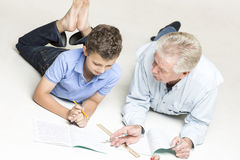 Grandfather helps his grandson with homework Stock Photography
