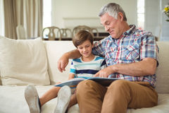 Grandfather with her grandson reading book on sofa Stock Image