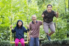 Grandfather with his grandchildren play with swings Stock Image