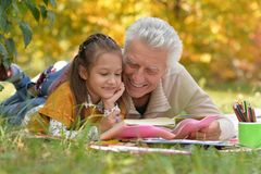 Grandfather and  granddaughter reading book. Grandfather and his granddaughter reading book outdoor Royalty Free Stock Photos