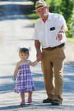 Grandfather with his granddaughter are on the road Stock Photography
