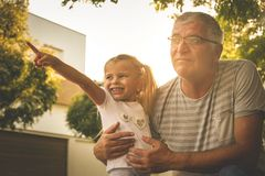 Grandfather with his granddaughter on street looking something fanny. Royalty Free Stock Photo