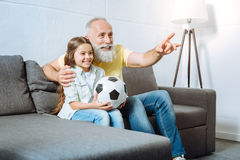 Grandfather and his granddaughter watching football together royalty free stock images