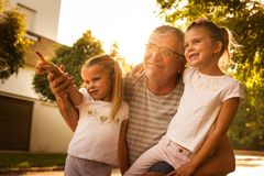 Grandfather with his granddaughters on street looking something fanny. Royalty Free Stock Image