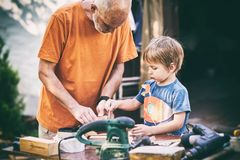 Grandfather and his grandson having fun in the outdoor workshop Stock Images
