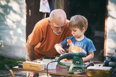 Grandfather and his grandson having fun in the outdoor workshop Stock Image
