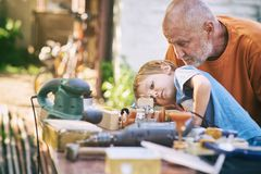 Grandfather and his grandson having fun in the outdoor workshop Royalty Free Stock Images