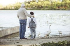 Grandfather With His grandson on the lake stock photo