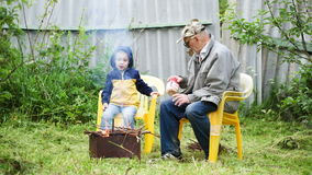 Grandfather and his grandson sitting by the fire Stock Photo