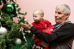 Grandfather with his grandson touching christmas tree Royalty Free Stock Image