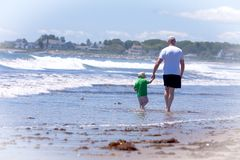 Grandfather with his grandson walking on a beach Royalty Free Stock Image