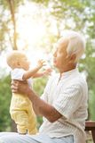 Grandfather playing with grandson at outdoor bench. Royalty Free Stock Photo