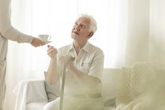 Grandfather holding a cane and getting a tea from his wife royalty free stock photos