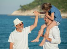 Grandfather holding girl s hand. While she is riding her father s shoulders on a sea beach Stock Photo