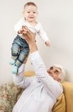 Grandfather holding grandson while sitting on sofa Stock Photos