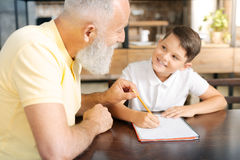 Grandfather holding grandsons pencil while helping him with homework Stock Photos