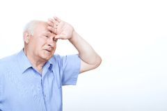 Grandfather holding hand on the forehead Stock Photo