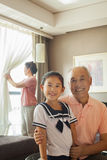 Grandfather holding her granddaughter, grandmother in the background Stock Photos