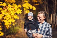 Grandfather holding his grandchild on arm, autumn Stock Image