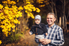 Grandfather holding his grandchild on arm, autumn Stock Photo