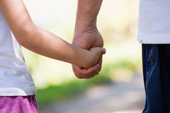 Grandfather holding his granddaughter hand in the forest royalty free stock photos