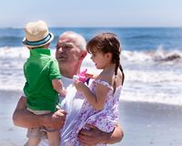 Grandfather holding his grandkids. On a beach vacation Royalty Free Stock Image