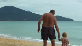Grandfather holding little girls hand and walks on the beach stock footage