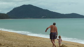 Grandfather holding little girls hand and walks on the beach stock video