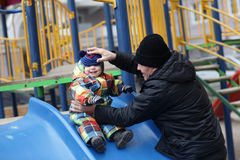Grandfather holding toddler on slide Stock Image