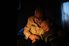 Grandfather hugs his grandson near fireplace Royalty Free Stock Photography