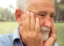 Grandfather keeping hands at he face and sighing heavily. Close up Side view Slow motio, emotions and feelings royalty free stock photos