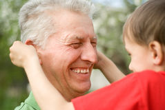 Grandfather keeps his grandson. In an outdoor Stock Photo