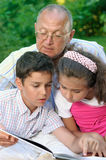 Grandfather and kids reading book. Happy grandfather and kids reading book outdoors Royalty Free Stock Photo