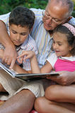 Grandfather and kids reading book. Outdoors Royalty Free Stock Photos