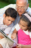 Grandfather and kids reading book. Outdoors Stock Photography