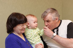 Grandfather kisses hand of baby Royalty Free Stock Photo