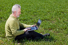 Grandfather with a laptop. Grandfather with a notebook on a grass Royalty Free Stock Photo