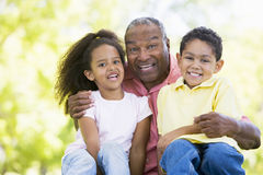 Grandfather laughing with grandchildren. Outside stock images